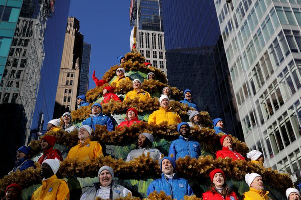 People sing carols in the Macy's Singing Christmas Tree on Sixth Avenue during the Macy's Thanksgiving Day Parade in Manhatta