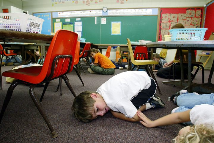 Kindergarten students in Hawaii lie on the floor during a classroom lockdown drill in 2003.