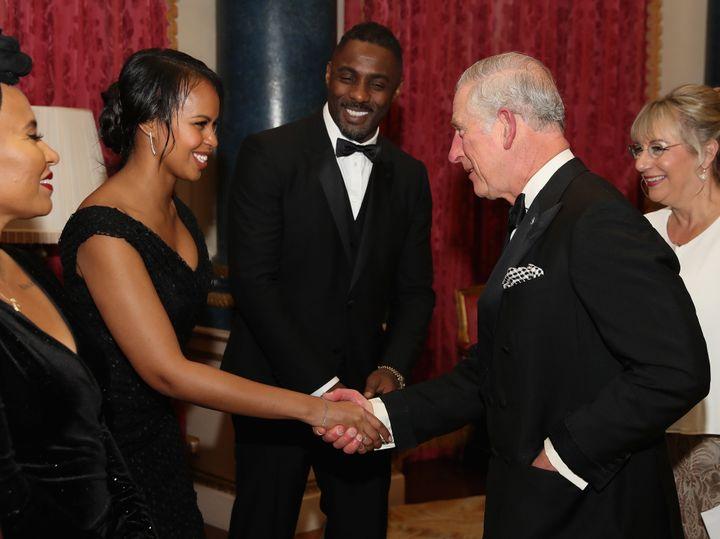 Prince Charles greets Sabrina Dhowre as Idris Elba looks on.