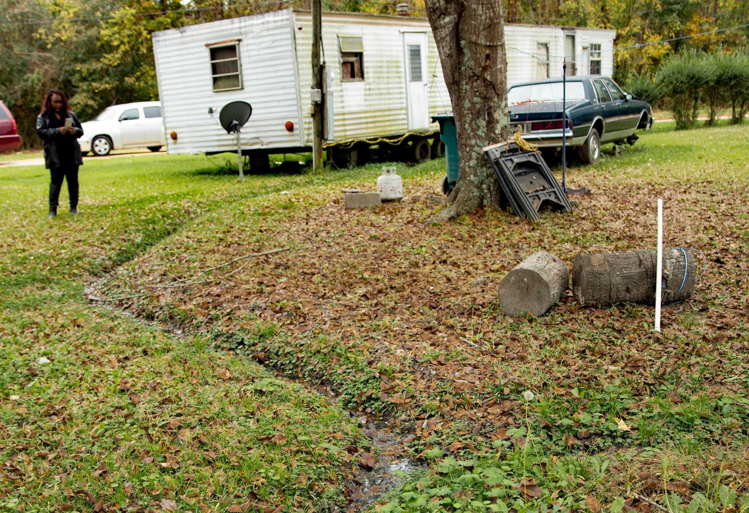 An open sewer carries waste from a mobile home toward the woods at the edge of the property.