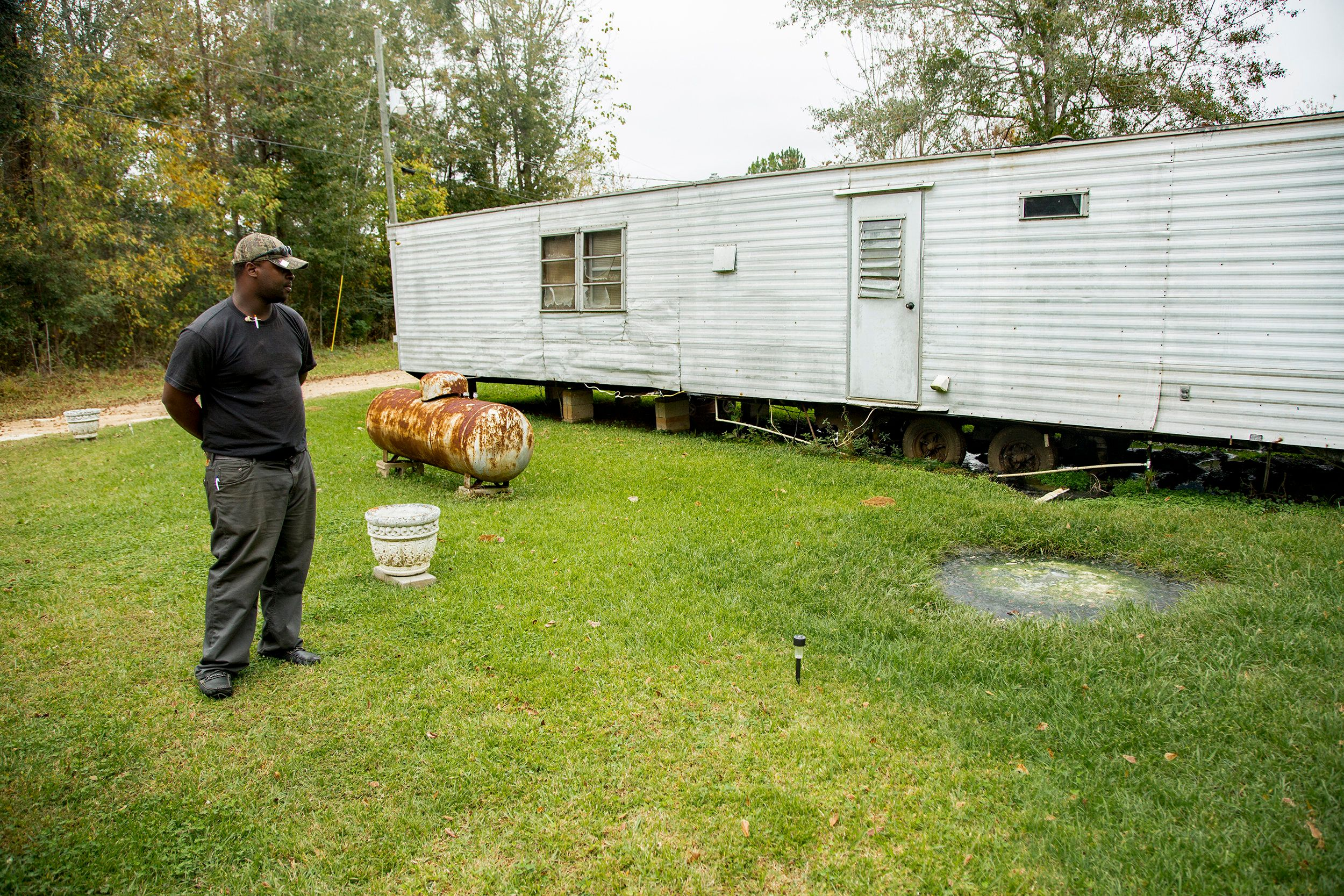 Community activist Aaron Thigpen examines raw waste pooling next to a mobile home.
