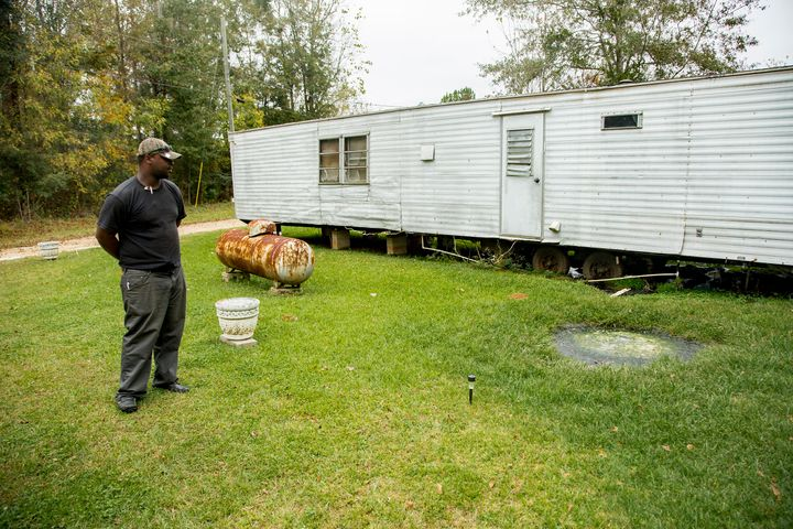 Community activist Aaron Thigpen examines raw waste pooling next to a mobile home in Lowndes County, Alabama.