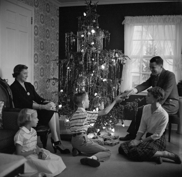 A boy distributes presents to his family in the 1950s.