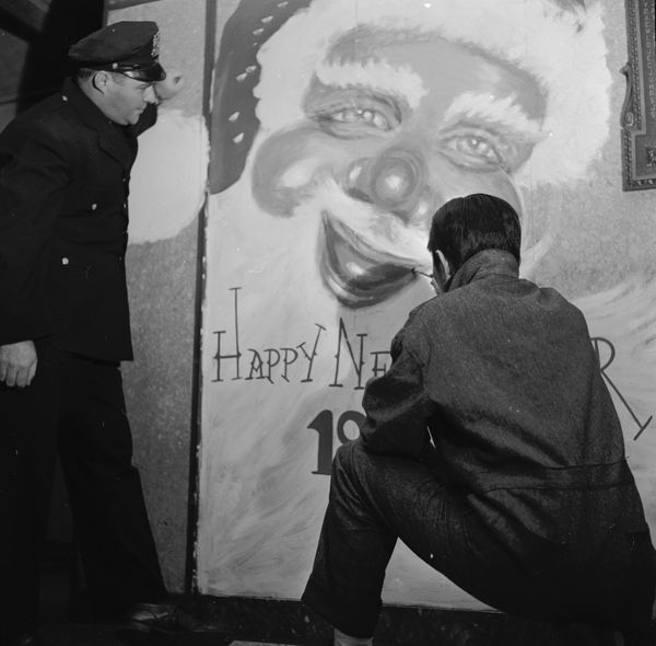 An inmate at New York's Rikers Island jail painting a huge Santa Claus on a wall in 1955.