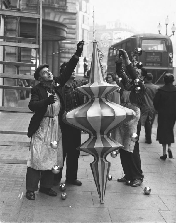 Men fasten globes to one of the large Christmas lanterns ready to be erected in Regent Street in London.