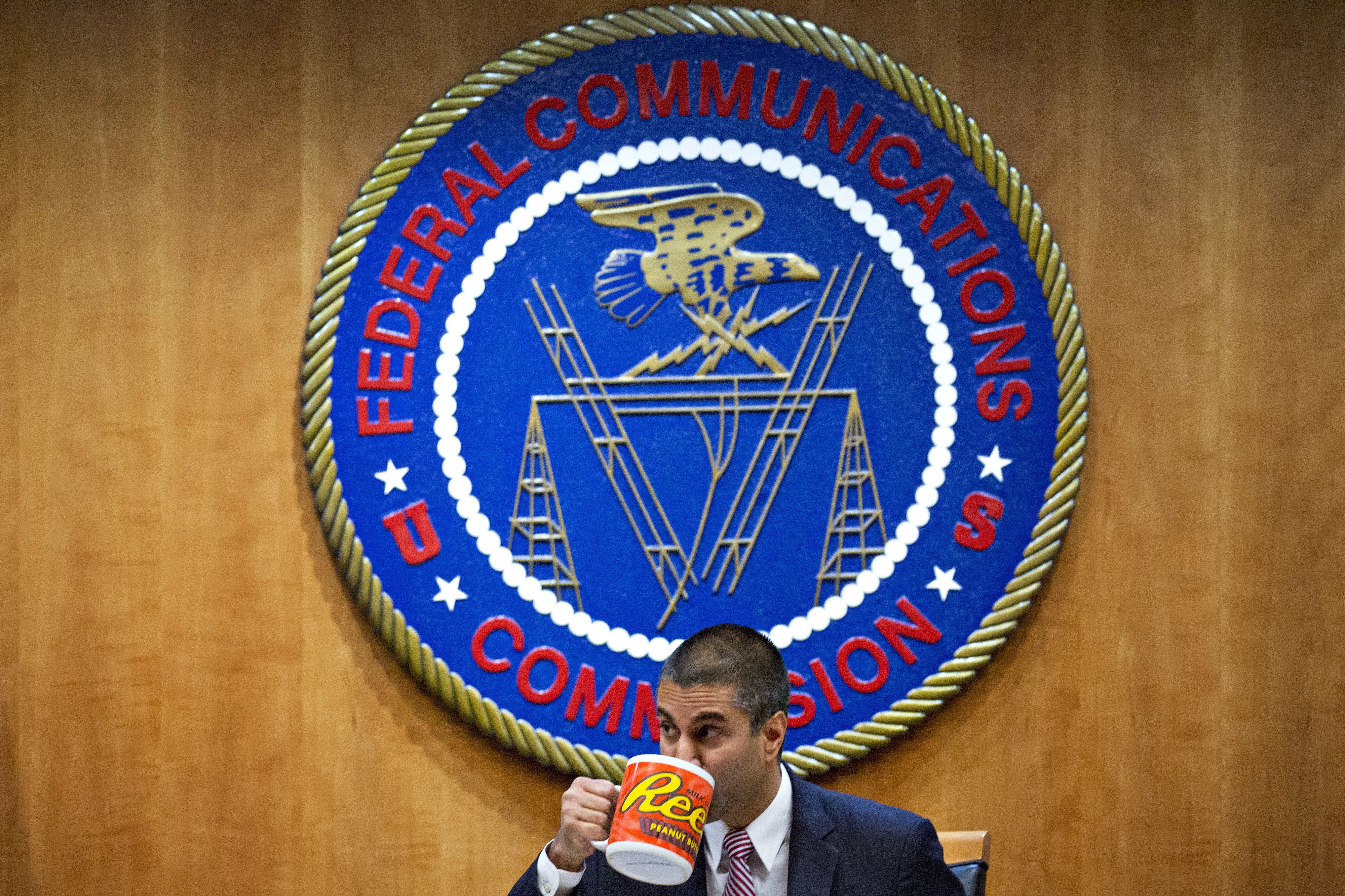 Ajit Pai, chairman of the Federal Communications Commission (FCC), drinks from an oversized coffee mug during an open commission meeting in Washington, D.C., U.S., on Thursday, Dec. 14, 2017. The FCC is slated to vote to roll back a 2015 utility-style classification of broadband and a raft of related net neutrality rules, including bans on broadband providers blocking and slowing lawful internet traffic on its way to consumers. Photographer: Andrew Harrer/Bloomberg via Getty Images