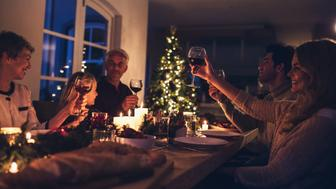 Extended family toasting wine at christmas dinner. Happy family enjoying christmas candle light dinner together at home.