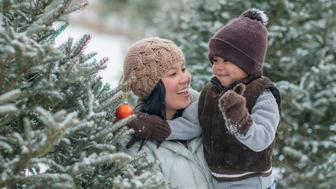 An Asian mother and son are outdoors on a snowy winter day. They are wearing hats, coats and gloves. They are putting a Christmas ornament onto a tree.