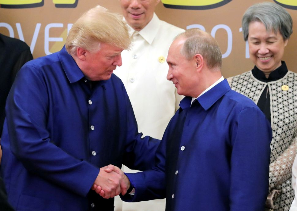 Trump and Putin shake hands as they take part in a family photo at the APEC summit in Danang, Vietnam, onNov. 10.