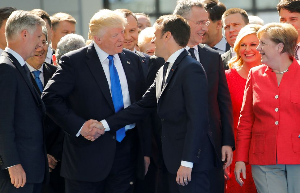 Trump jokes with French President Emmanuel Macron about their handshakes at the start of the NATO summit at their new headqua
