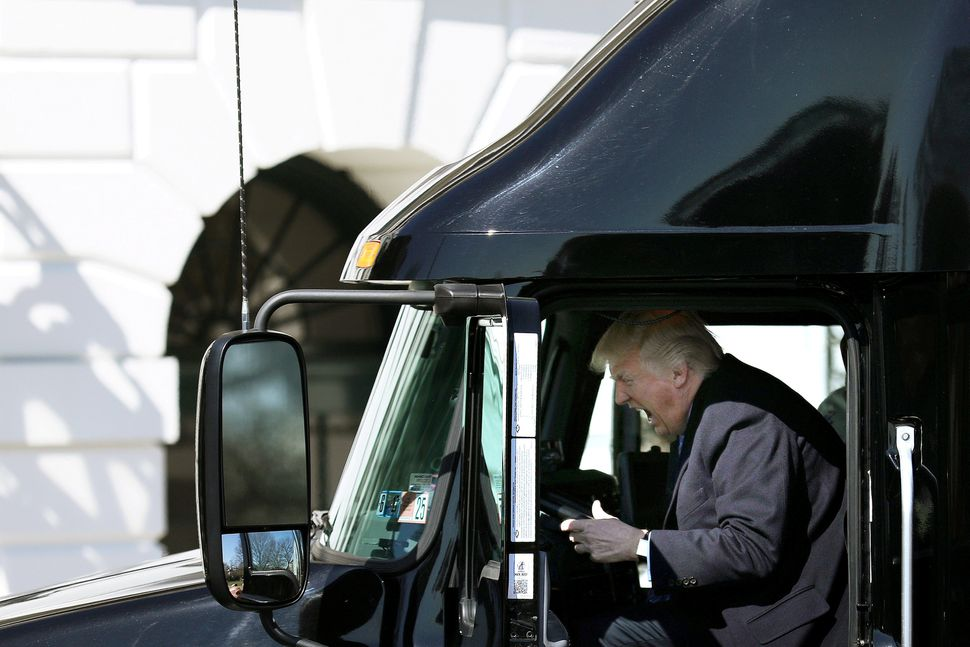 Trump reacts as he sits in a truck on March 23 while welcoming truckers and CEOs to attend a meeting at the White H