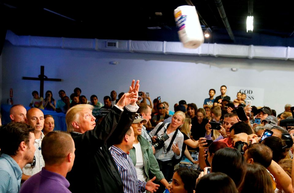 Trump throws rolls of paper towels into a crowd of Puerto Rico residents affected by Hurricane Maria as he visits Calgar