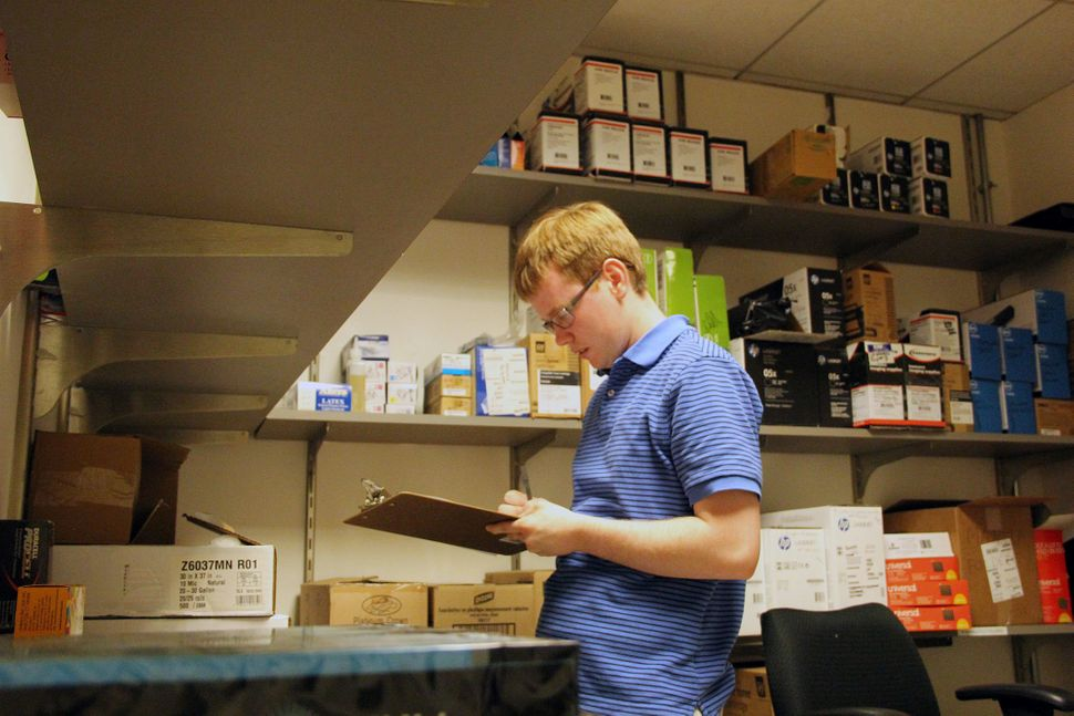 Peter O'Halloran checks supplies at his job. O'Halloran works full-time at a nonprofit in Philadelphia.