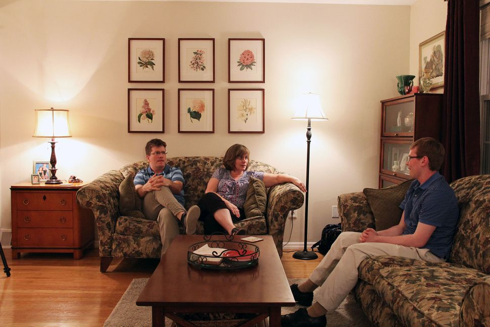 Peter O'Halloran sits with his family in their house in the suburbs of Philadelphia. He is saving money to buy his own home.