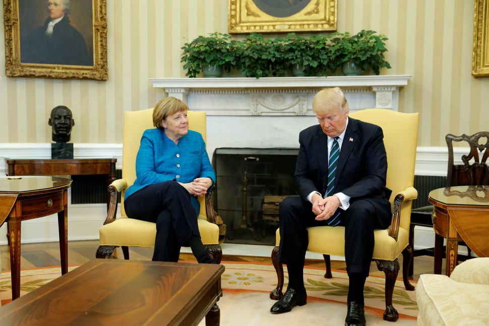 Trump and German Chancellor Angela Merkel wait for reporters to enter the room before their meeting in the Oval Office o