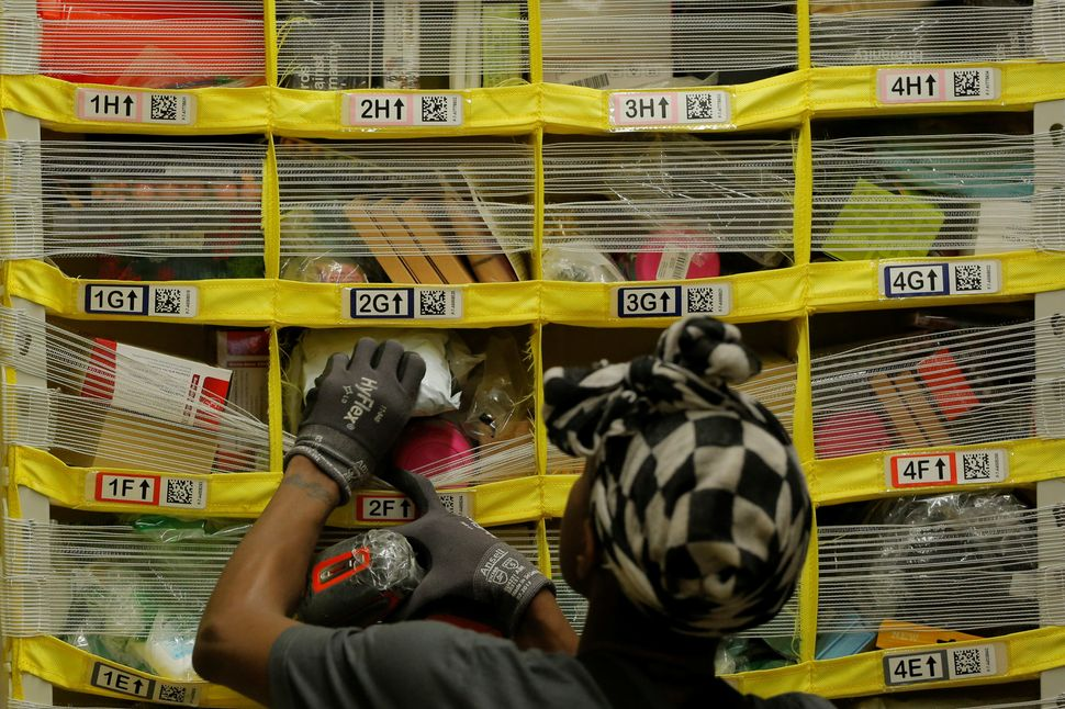 A worker sorts products into bins inside of a large Amazon fulfillment center.