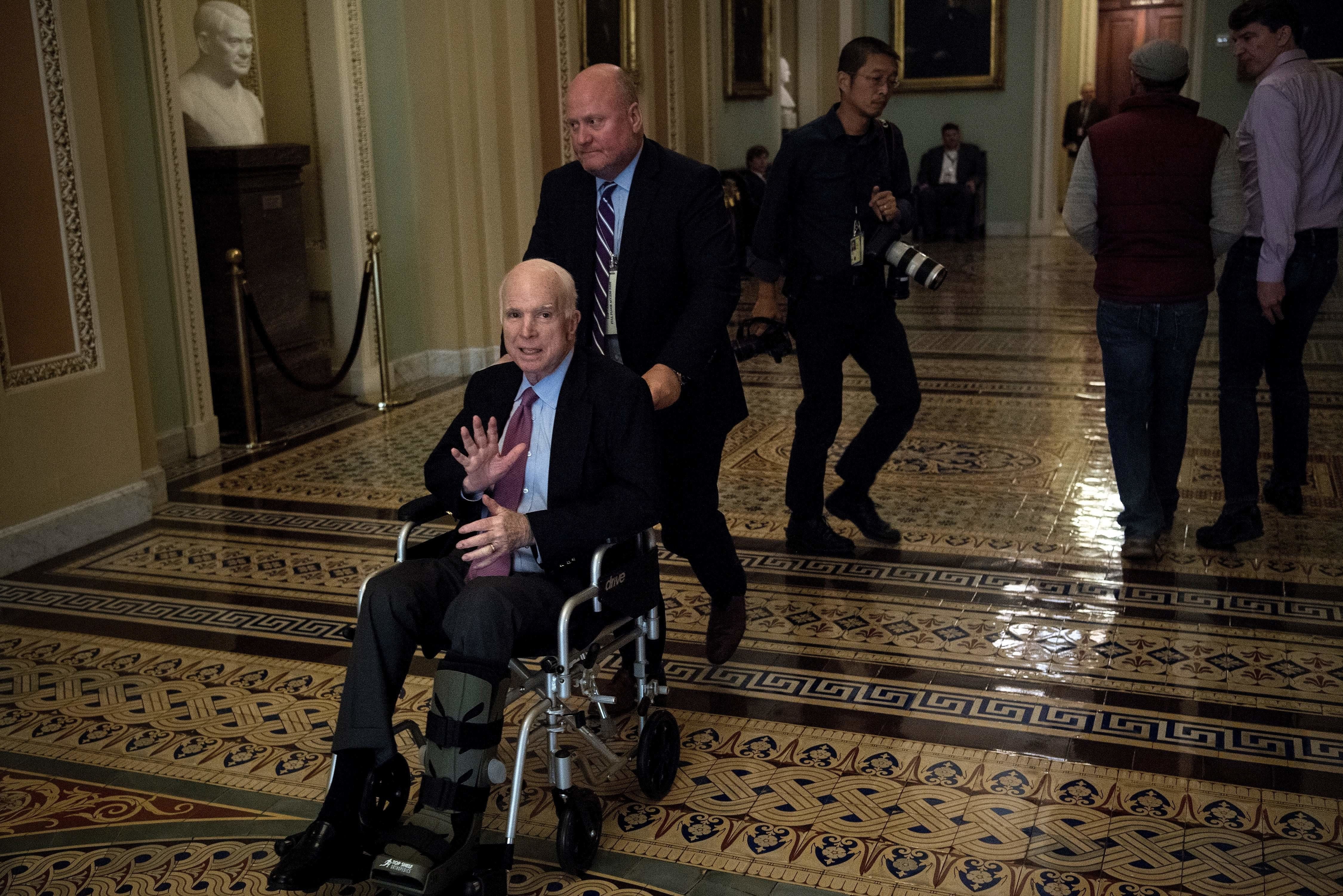 Senator John McCain (R-AZ) uses a wheelchair on Capitol Hill December 1, 2017 in Washington, DC. Donald Trump's tax reform plan has overcome pockets of resistance within Republican ranks, US senators said Friday, setting up a vote that could provide the president with his first major legislative victory.'We have the votes,' Senate Majority Leader Mitch McConnell told reporters as he entered the chamber.  / AFP PHOTO / Brendan Smialowski        (Photo credit should read BRENDAN SMIALOWSKI/AFP/Getty Images)