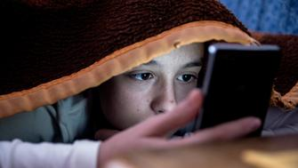 girl in bed texting on smartphone
