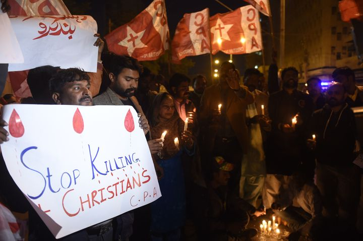 Pakistani Christians hold banners and lighted candles during a protest in Karachi on December 17, 2017, after a suicide bombe