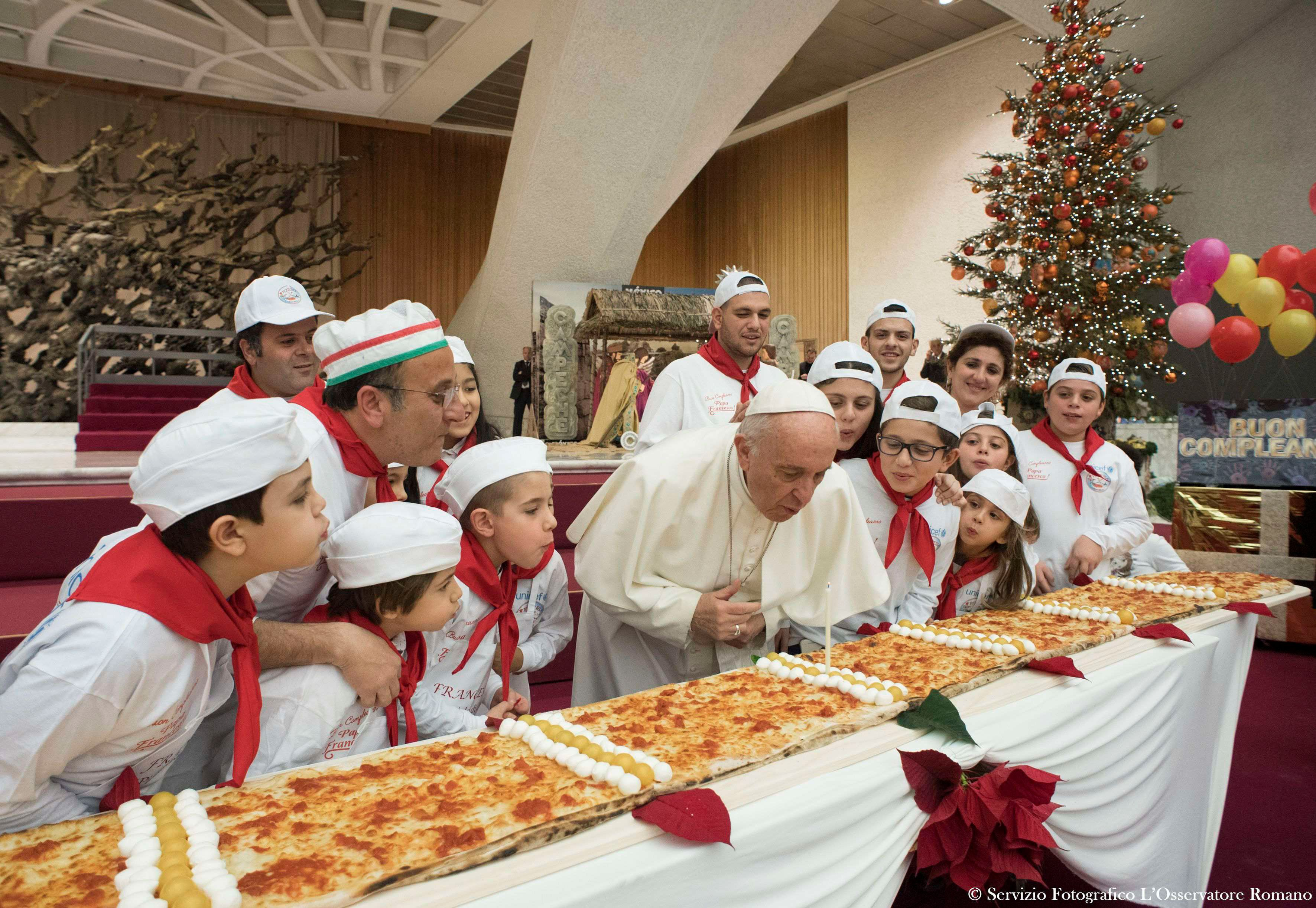 Pope Francis blows on a candleto celebrate his birthday during a special meeting at Paul VI hall at the Vatican on Dec.