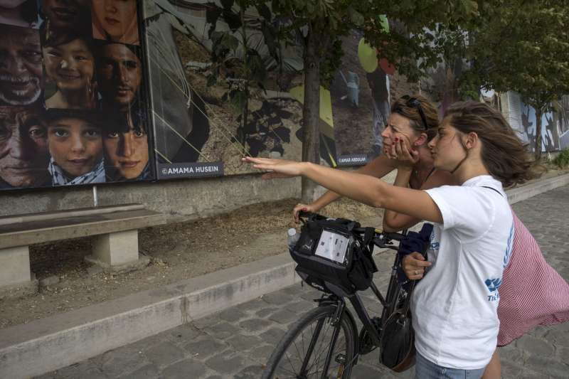 <em>A UNHCR volunteer indicates to a visitor some of the main themes of Reza's exhibition along the Seine's shore in Paris. <