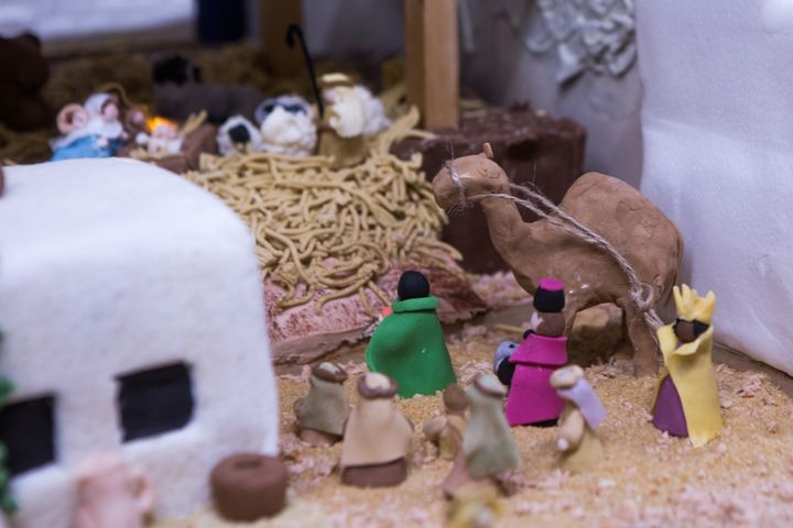Shepherds and three wise men approach the manger scene.