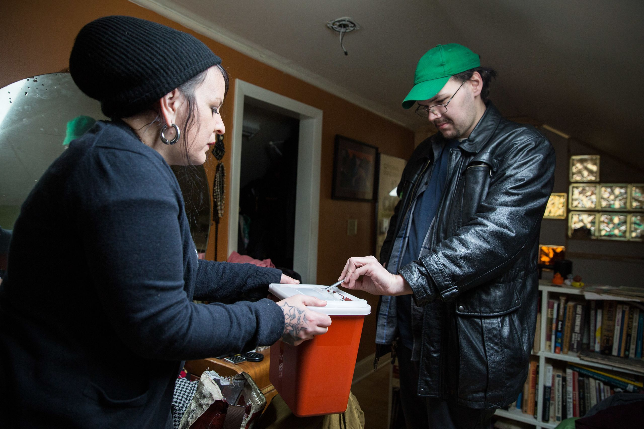 Tilley holds out a safe medical waste container for Joe Worpek to deposit his used syringes.