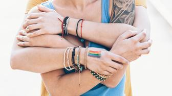 Close up of two young women embracing. Both wear casual clothes, bracelets. One with rainbow flag drawned on hand, other with arm tattoo.
