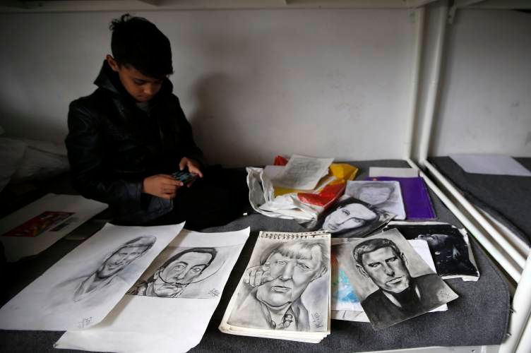 "<em>Farhad Nouri, ""The Little Picasso"", sitting among some of his portraits.</em>"