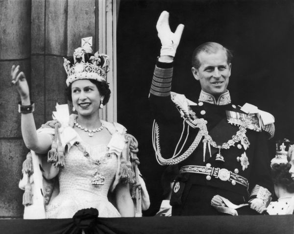 The newly crowned Queen Elizabeth II and Philip, Duke of Edinburgh, wave at the crowds from the balcony at Buckingham Palace.