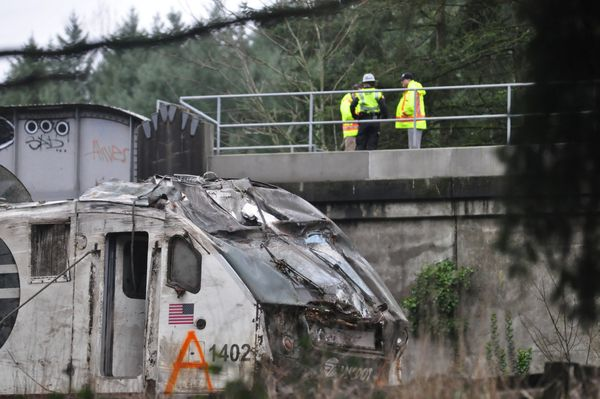 First responders are seen at the scene of an Amtrak passenger train which derailed and is hanging from a bridge over the inte