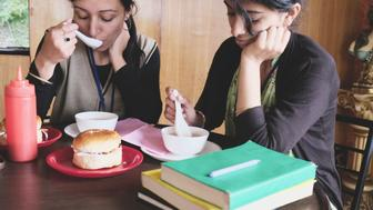 Teenagers eating junk food in college canteen.