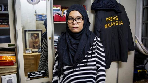 Diyana Kamalludden, 36, poses for a photograph with her late husband's, Rostam Ramli, windbreaker in a room where she keeps personal belongings and of her late husband's after an interview with Huffington Post in Kuala Lumpur, Malaysia, Monday, Dec. 6, 2017. (Joshua Paul for Huffington Post)