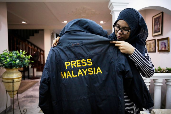 Diyana holds up her late husband's windbreaker.