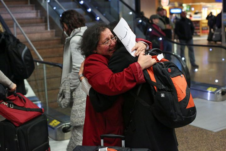 Neeta Hull (L) hugs her cousin Afsaneah Hashemi (R) following Hashemi's arrival from Iran during a pause in Trump's travel ba