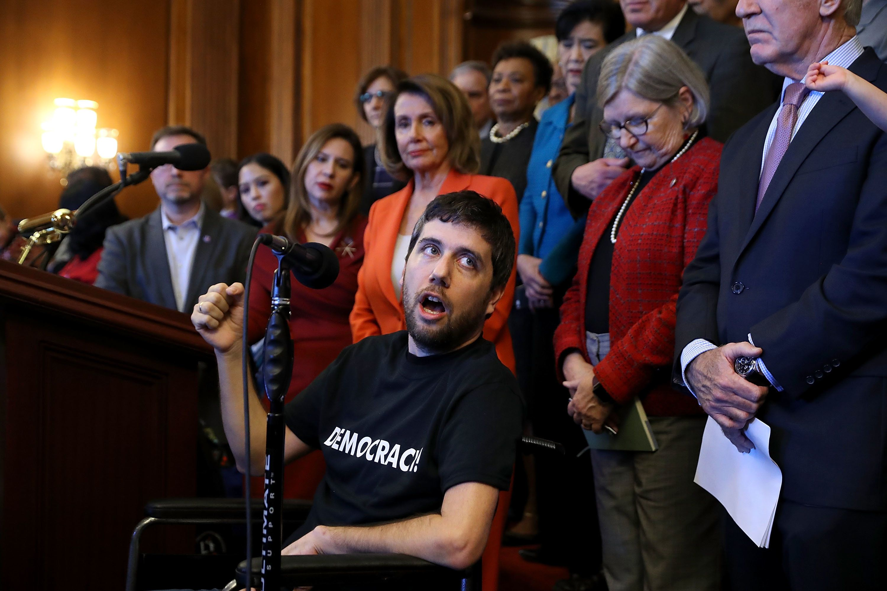 WASHINGTON, DC - DECEMBER 19:  Ady Barkan (C), who lives with Amyotrophic Lateral Sclerosis, delivers remarks during a rally organized by House Minority Leader Nancy Pelosi (D-CA) in the Rayburn Room at the U.S. Capitol December 19, 2017 in Washington, DC. Pelosi and fellow House Democrats invited people with complex medical needs and disabilities who rely on Medicare to rally with them before the House was to vote on the Tax Cuts and Jobs Act. (Photo by Chip Somodevilla/Getty Images)