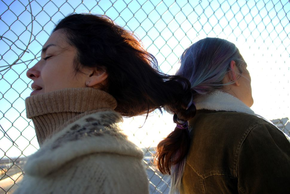 Women activists from Mexico and the United States braid their hair together in a silent demonstration against the immigration