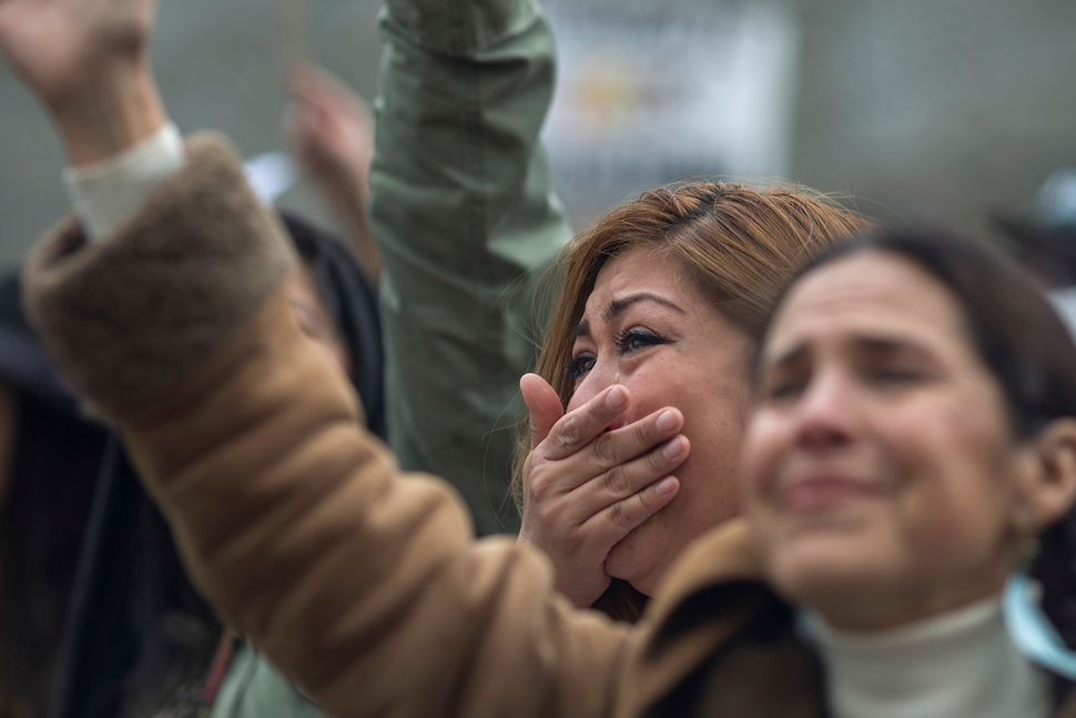 Vanessa Chairee cries as women call up toward immigrants detained at the Federal Bureau of Prisons Metropolitan Detention Cen