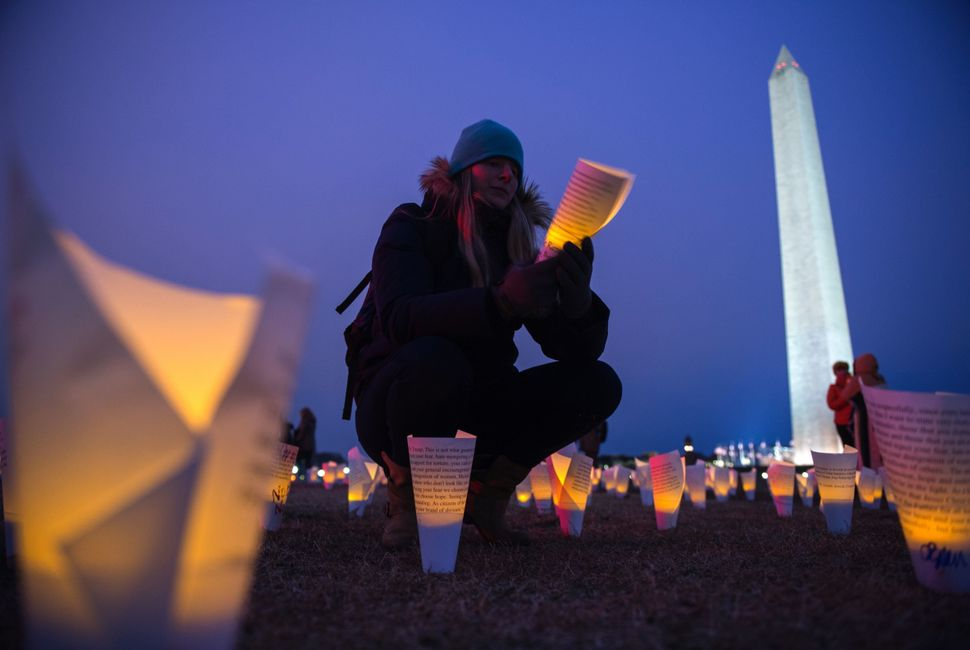 A woman reads messages on paper cones with electric candles in them at the Washington Monument during a protest against Trump