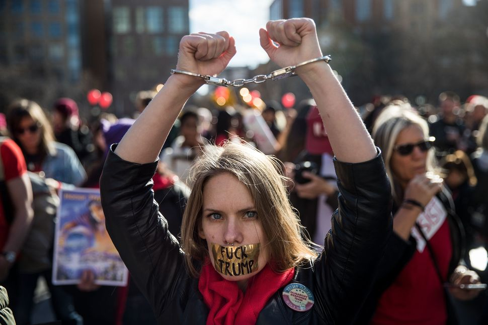 A woman holds up her handcuffed wrists as she attends a rally to mark International Women's Day in New York City's Washington