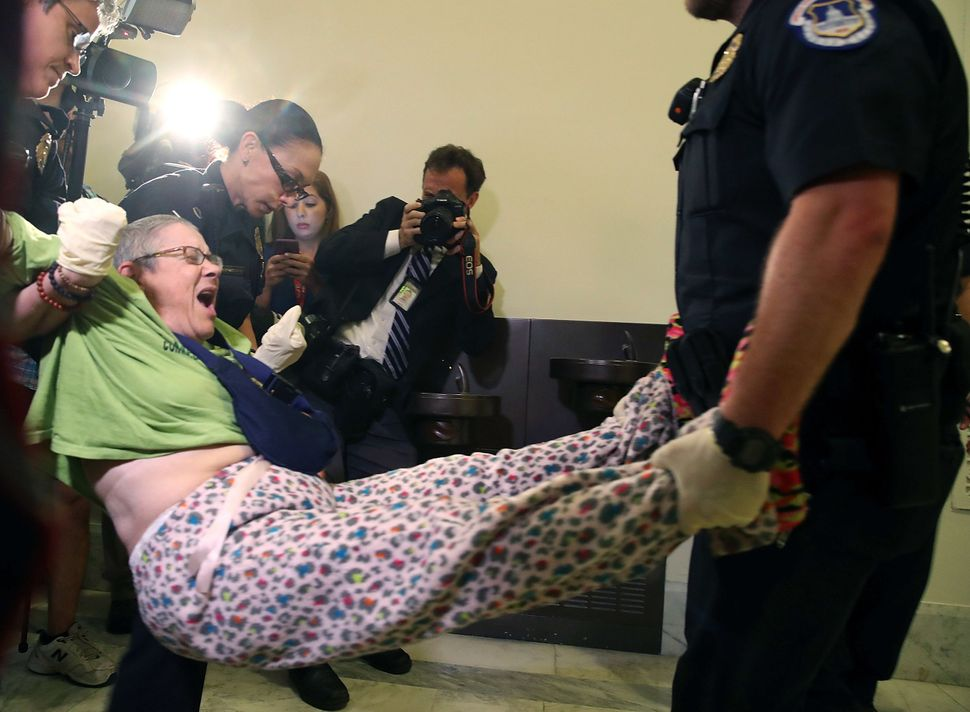 U.S. Capitol Police remove a woman from a protest in front of the office of Senate Majority Leader Mitch McConnell (R-Ky.) on