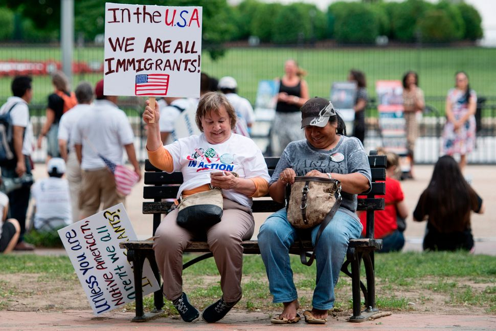 Two women with placards sit on a park bench as demonstrators with Casa in Action and Service Employee International Union 32B