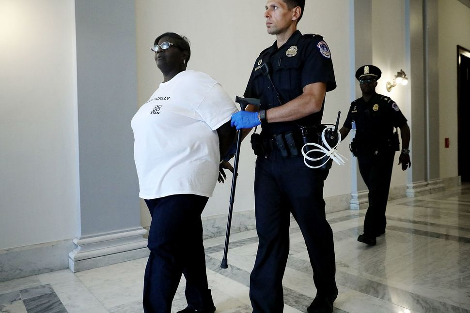A U.S. Capitol Police officer carries a woman's cane after arresting her for protesting against the Republican health care re