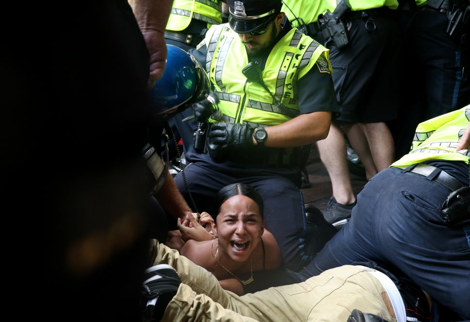 "A woman is arrested during a confrontation on Washington Street following the ""Boston Free Speech"" rally and counterprotest o"