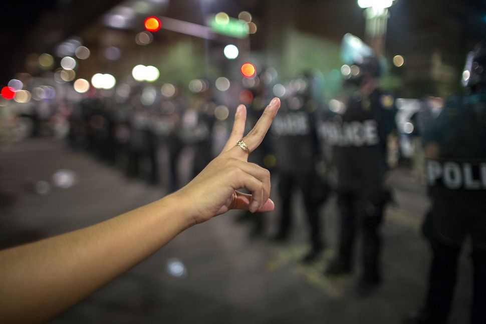 A woman makes a peace sign before a line of police preparing to advance upon demonstrators after a Trump rally at the Phoenix