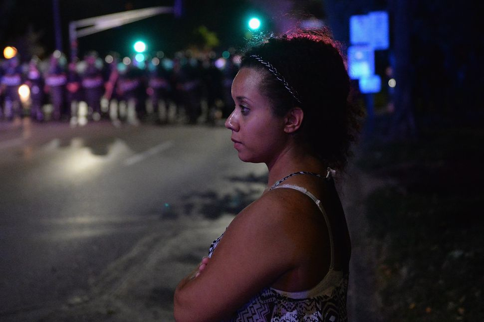 "A woman watches as law enforcement officers secure an area during a protest action following a ""not guilty"" verdict for forme"