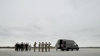 DOVER, DE - NOVEMBER 08:  Members of the official party and a U.S. Army carry team stand at attention as the transfer case containing the remains of Sgt. 1st Class Stephen B. Cribben are moved at Dover Air Force Base November 8, 2017 in Dover, Delaware. Assigned to the 2nd Battalion, 10th Special Forces Group, Cribben, 33, was killed in Logar, Afghanistan, when his unit was engaged in what the Pentagon calls 'combat operations.'  (Photo by Chip Somodevilla/Getty Images)