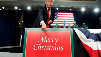 "U.S. President Donald Trump points to a ""Merry Christmas"" placard on the stage as he arrives to deliver remarks on tax reform in St. Louis, Missouri, U.S. November 29, 2017. REUTERS/Kevin Lamarque"