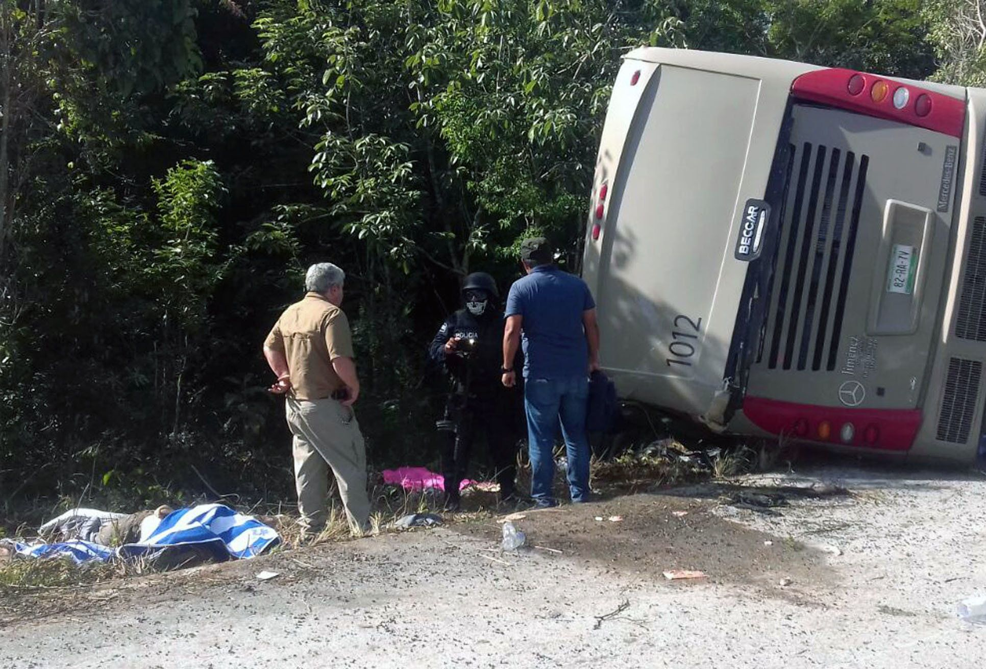 Mexican police officers and paramedics work in the scene of a road accident, where a bus driving tourists to Chacchoben archaeological zone overturned between El Cafetal and Mahahual, in Quintana Roo state, Mexico on December 19, 2017. At least eleven tourists who arrived in the Mexican Caribbean on a US cruise ship were killed and another 20 injured in a road accident on Tuesday when they were heading to an archaeological zone, the Quintana Roo state government reported. / AFP PHOTO / Manuel Jesús ORTEGA CANCHE        (Photo credit should read MANUEL JESUS ORTEGA CANCHE/AFP/Getty Images)