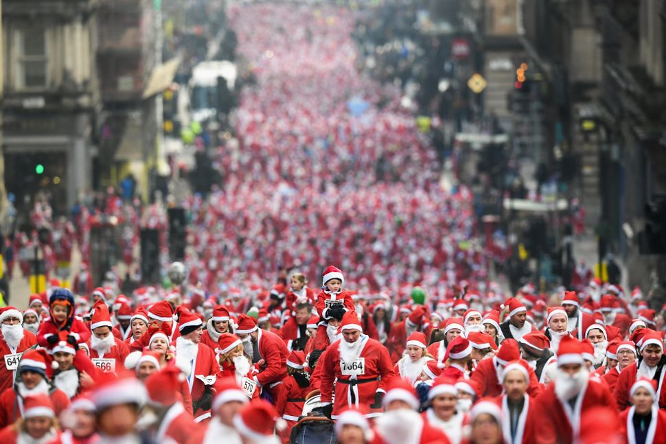 Over 8,000 members of the public take part in Glasgow, Scotland's annual Santa dash and make their way up St. Vincent St